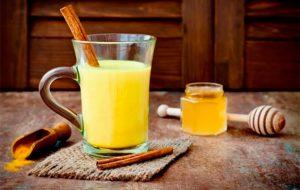 Vaso de leche dorada con una rama de canela - vidalaurayoga.es