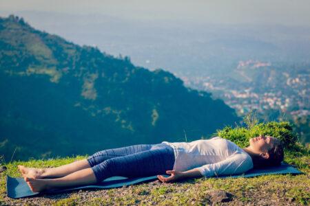 Mujer en savasana, tumbada boca arriba